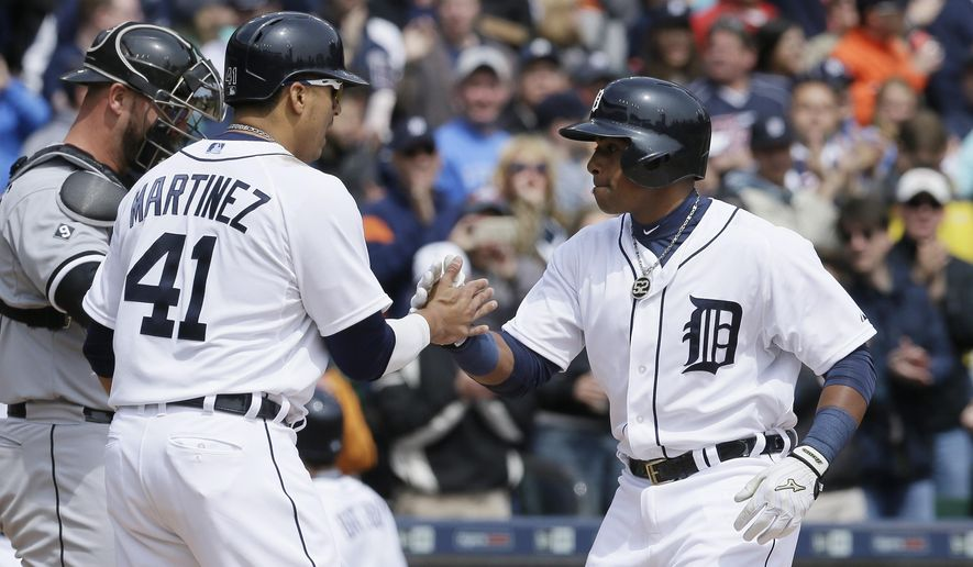 Detroit Tigers' Yoenis Cespedes, right, is congratulated by teammate Victor Martinez after they both scored on Cespedes' two-run home run in the third inning off Chicago White Sox starting pitcher Jose Quintana in a baseball game, Sunday, April 19, 2015, in Detroit. (AP Photo/Carlos Osorio)