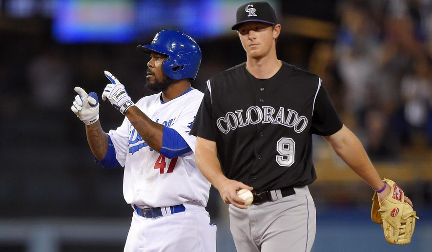 Los Angeles Dodgers' Howie Kendrick points toward the dugout after hitting an RBI double as Colorado Rockies second baseman DJ LeMahieu walks away during the seventh inning of a baseball game, Saturday, April 18, 2015, in Los Angeles. (AP Photo/Mark J. Terrill)