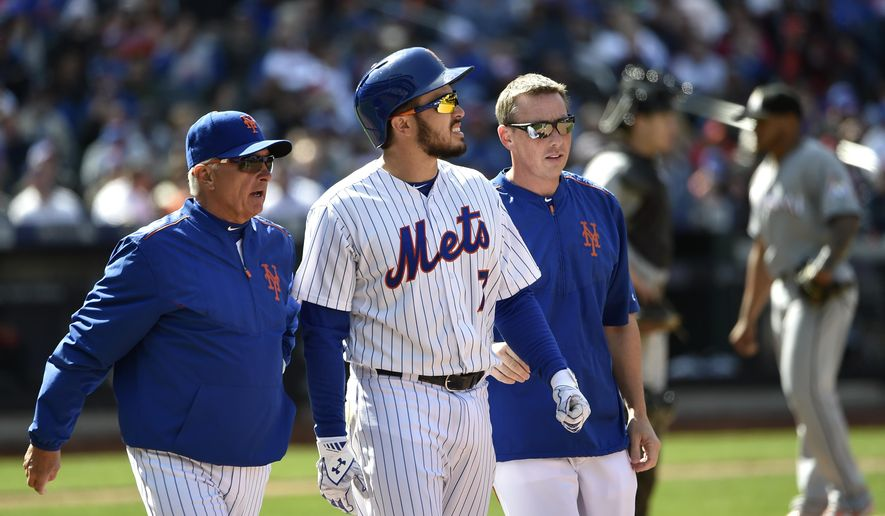 New York Mets manager Terry Collins, left, and a Mets trainer talk with catcher Travis d'Arnaud (7) after he was hit by a pitch thrown by Miami Marlins relief pitcher A.J. Ramos, right, in the seventh inning of a baseball game at Citi Field on Sunday, April 19, 2015, in New York. d'Arnaud left the game with a fractured right hand. (AP Photo/Kathy Kmonicek)