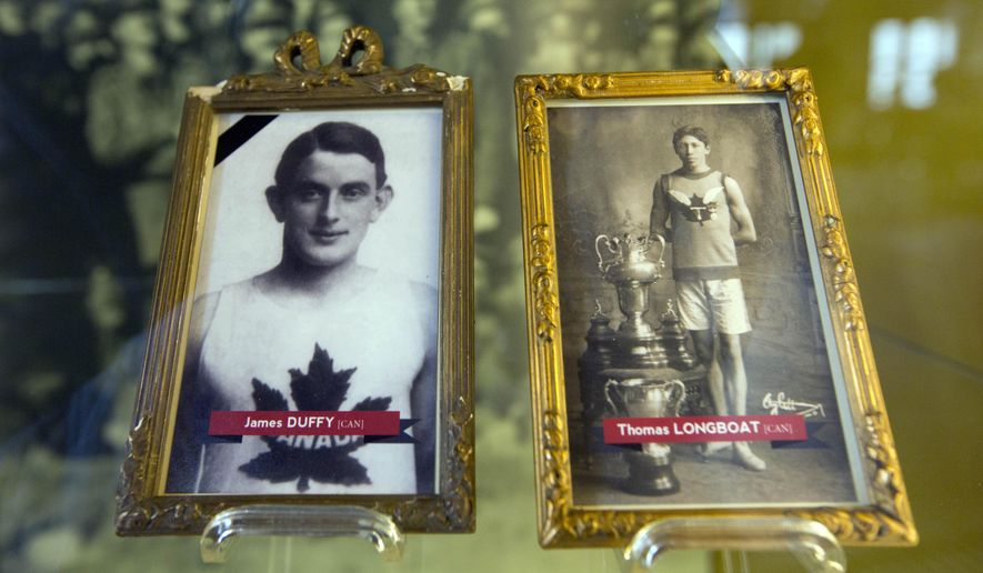 In this photo taken on June 14, 2014, illustrations of World War I soldiers and Boston Marathon winners James Duffy, 1914, and Tom Longboat, 1907, are framed behind glass on exhibit at the In Flanders Fields Museum in Ypres, Belgium. Duffy died on the battlefield of Belgium in 1915 while Longboat survived the war and was able to return home. (AP Photo/Virginia Mayo)