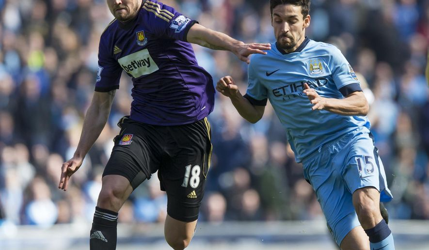 Manchester City's Jesus Navas, right, fights for the ball against West Ham United's Carl Jenkinson during the English Premier League soccer match between Manchester City and West Ham United at the Etihad Stadium, Manchester, England, Sunday April 19, 2015. (AP Photo/Jon Super)