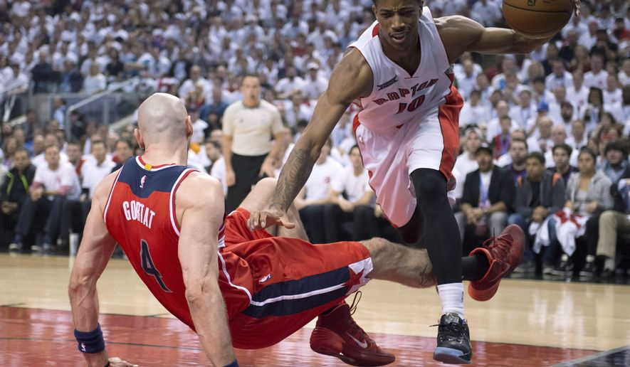 Toronto Raptors' DeMar DeRozan (10) is fouled on his way to the hoop by Washington Wizards' Marcin Gortat (4) during the first half in Game 1 in the first round of the NBA basketball playoffs in Toronto, Saturday, April 18, 2015. (Frank Gunn/The Canadian Press via AP)   MANDATORY CREDIT