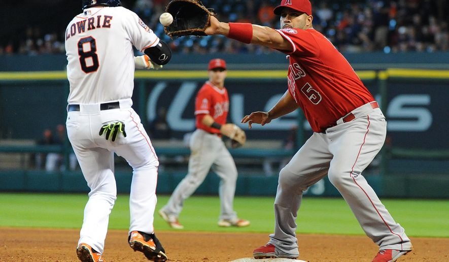 Houston Astros Jed Lowrie (8) reaches first on a dropped third strike in front of Los Angeles Angels first baseman Albert Pujols in the fifth inning of a baseball game Sunday, April 19, 2015, at Minute Maid Park in Houston. (AP Photo/Eric Christian Smith)