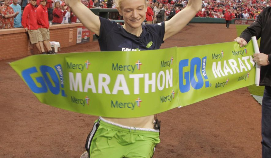 Andrea Karl, the Women's winner of the 15th Annual Go! St. Louis marathon, breaks the finish line tape prior to a baseball game between the St. Louis Cardinals and the Cincinnati Reds, Sunday, April 19, 2015 in St. Louis.  Karl was unable to break the tape on the day of the marathon after a different woman, who was later to have been disqualified for cheating, broke the tape. (AP Photo/Tom Gannam)