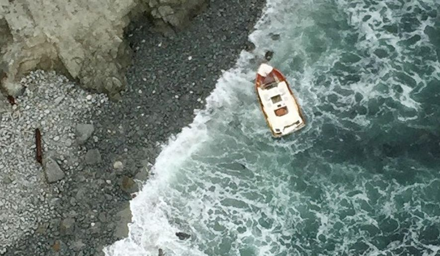 This April 18, 2015 aerial photo from the Sonoma County, Calif., Sheriff's Office shows a 21-foot boat overturned in the rocks near Tomales Point in Marin County, Calif. Authorities say two people have been found dead and two others remain missing following the boating accident off the Northern California coast. The Sonoma County Sheriff's office says the search for the fishing party was launched Friday evening after someone reported that the boaters had not returned to dock near Bodega Bay. A Coast Guard crew spotted the boat Saturday morning. (Sonoma County Sheriff's Office via AP)