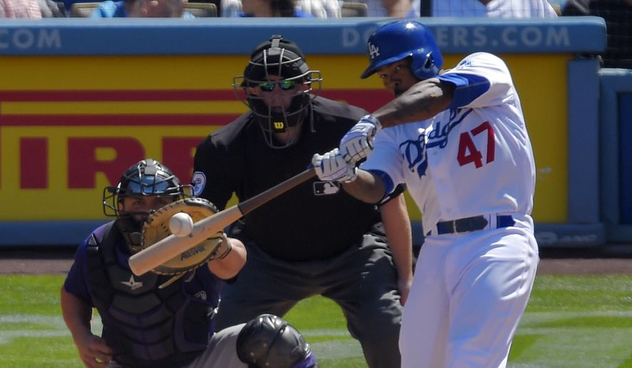 Los Angeles Dodgers' Howie Kendrick, right, hits a solo home run as Colorado Rockies catcher Michael McKenry, left, and home plate umpire Todd Tichenor watche during the fifth inning of a baseball game, Sunday, April 19, 2015, in Los Angeles. (AP Photo/Mark J. Terrill)