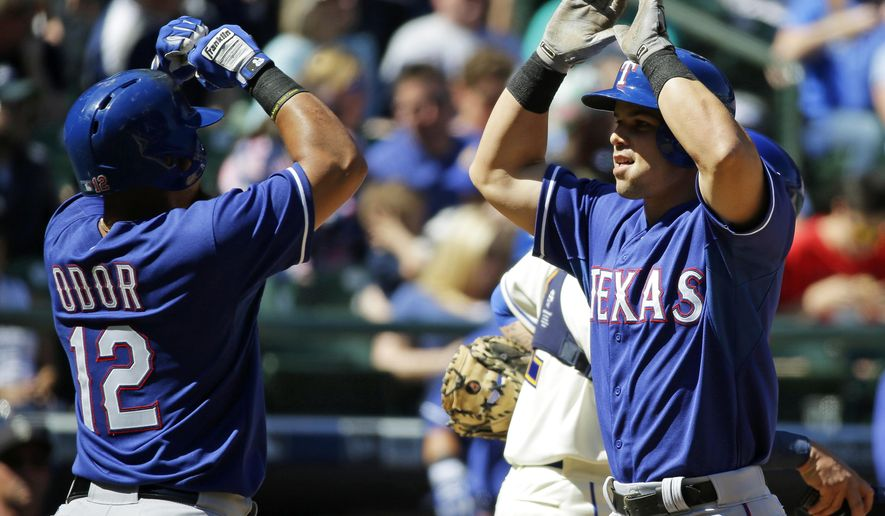 Texas Rangers 'Jake Smolinski, right, is greeted at the plate by Rangers' Rougned Odor, left, after Smolinski hit a two-run home run against the Seattle Mariners that scored Odor in the third inning of a baseball game, Sunday, April 19, 2015, in Seattle. (AP Photo/Ted S. Warren)