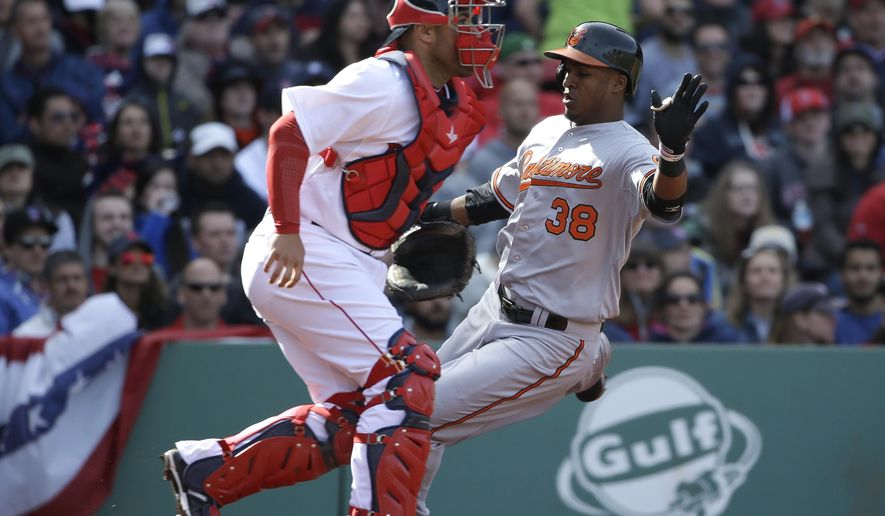 Baltimore Orioles' Jimmy Paredes, right, scores on a three-run double by teammate Adam Jones as Boston Red Sox catcher Sandy Leon, left, waits for the ball in the sixth inning of a baseball game Sunday, April 19, 2015, in Boston. (AP Photo/Steven Senne)