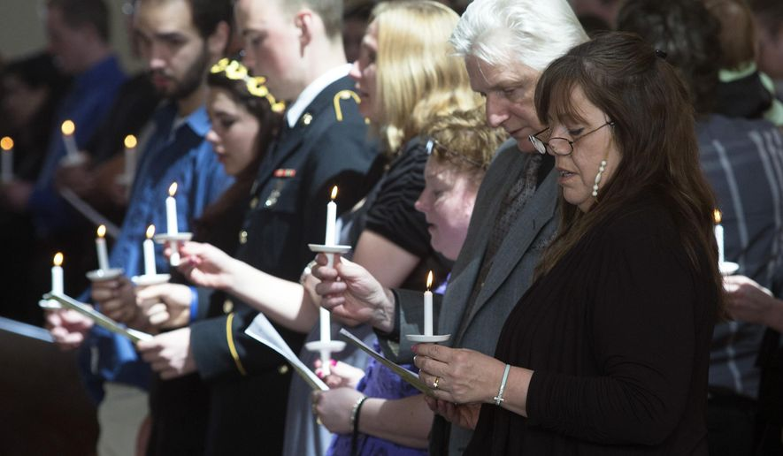 """Geraldine Schultz's family members sing """"Amazing Grace""""  and light candles at the conclusion of her funeral Saturday, April 18, 2015, at Westminster Presbyterian Church in Rockford, Ill. Schultz was killed in a tornado April 9. (Sunny Strader/Rockford Register Star via AP)"""