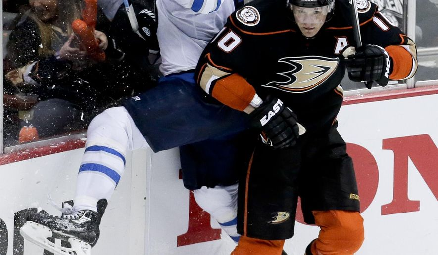 Anaheim Ducks right wing Corey Perry, right, checks Winnipeg Jets defenseman Mark Stuart during the second period of Game 2 of a first-round NHL hockey playoff series in Anaheim, Calif., Saturday, April 18, 2015. (AP Photo/Chris Carlson)