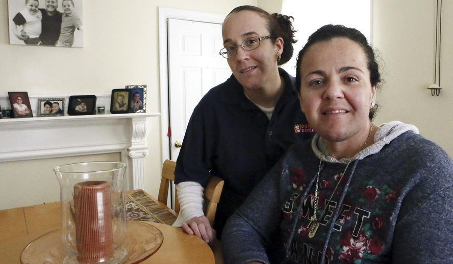 ADVANCE FOR USE SATURDAY, APRIL 18, 2015, AND THEREAFTER- In this March 26, 2015, photo, Susane Nunes, left, poses for a photo with her sister Dee Noonan in New Bedford, Mass. The sisters opted to have preventative surgeries because of their risk of breast cancer. (Mike Valeri/Standard Times via AP)