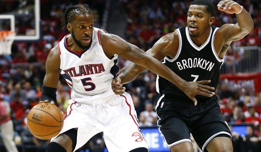 Atlanta Hawks forward DeMarre Carroll (5) drives against Brooklyn Nets forward Joe Johnson (7) in the first half of an NBA playoff basketball game  Sunday, April 19, 2015, in Atlanta.  (AP Photo/John Bazemore)