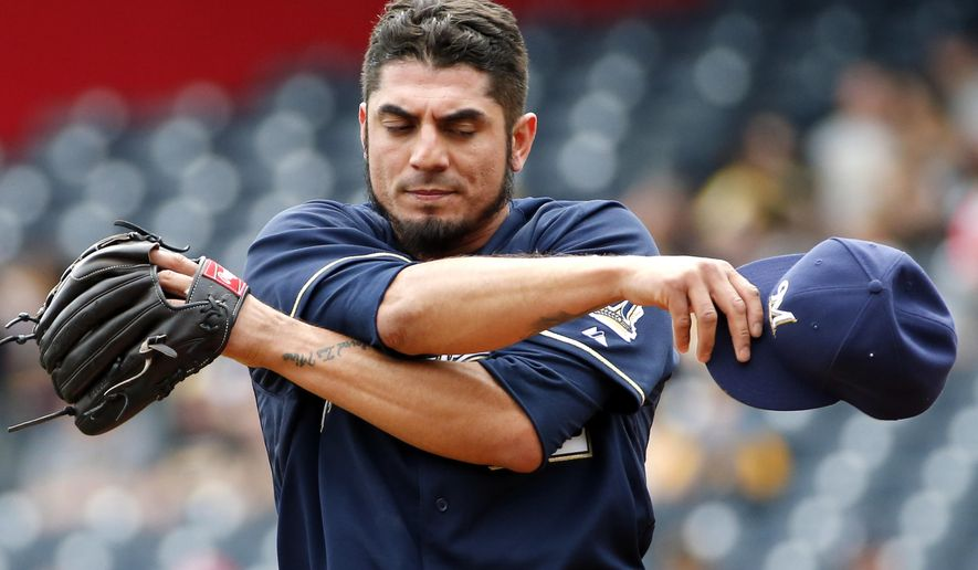 Milwaukee Brewers starting pitcher Matt Garza (22) finishes wiping his head in the first inning of a baseball game against the Pittsburgh Pirates in Pittsburgh, Sunday, April 19, 2015. (AP Photo/Gene J. Puskar)