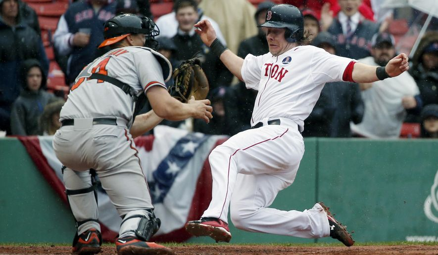 Boston Red Sox's Ryan Hanigan, right, scores as Baltimore Orioles' Ryan Lavarnway waits for the throw on a double by Dustin Pedroia during the sixth inning of a baseball game, Monday, April 20, 2015, in Boston. (AP Photo/Michael Dwyer)