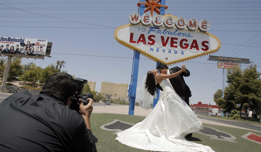 """FILE - In this July 7, 2007, file photo, Wedding photographer Sergio Lopez, left, take pictures of newly-weds Joseph Buangan and his wife Joyce, both of Torrance, Calif., with the """"Welcome to Fabulous Las Vegas"""" neon sign in the background in Las Vegas. Betty Willis, the woman who designed the iconic neon sign that has welcomed countless visitors to Las Vegas since 1959 has died. She was 91. (AP Photo/Jae C. Hong, File)"""