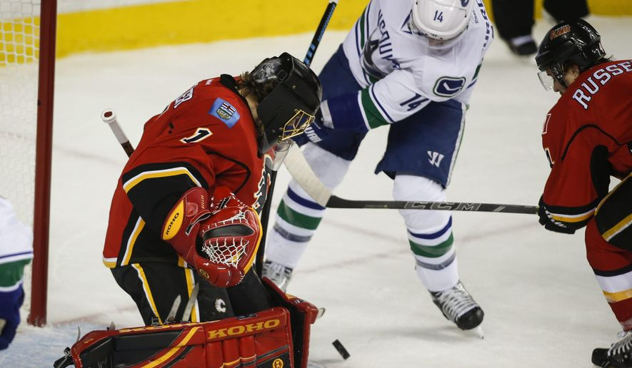 Vancouver Canucks' Alexandre Burrows, centre, tries to get the puck past Calgary Flames goalie Jonas Hiller, from Switzerland, during second period NHL first round playoff hockey action in Calgary, Sunday, April 19, 2015. (Jeff McIntosh/The Canadian Press via AP) MANDATORY CREDIT
