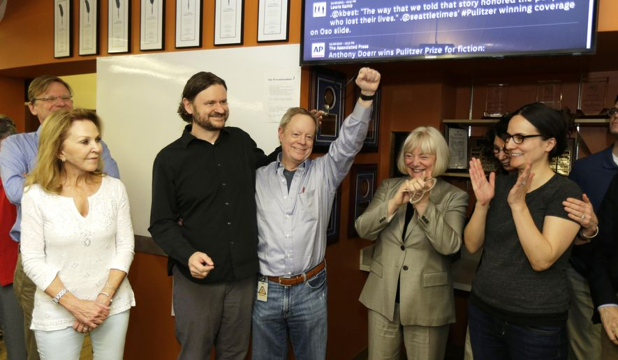 Frank Blethen, center, owner and publisher of the Seattle Times, cheers as he stands with his son Ryan Blethen, second from left, who is the Times' Assistant Managing Editor for Digital, and Frank Blethen's wife Charlene, far left, as they celebrate in the Seattle Times newsroom, Monday, April 20, 2015, after it was announced that the Times staff had won the Pulitzer Prize for breaking news reporting. Also shown is Times Editor Kathy Best, second from right, and multimedia specialist Courtney Riffkin, right. The Times won for its coverage of the mudslide in Oso, Wash., that killed 43 people, and its exploration of whether the disaster could have been prevented. (AP Photo/Ted S. Warren)