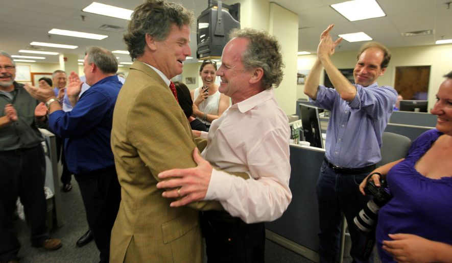 """Evening Post Industries Chairman of the Board Pierre Manigault, congratulates Doug Pardue after the Pulitzer prize announcement Monday April 20, 2015 in the newsroom of The Post and Courier in Charleston, S.C..  The Public Service gold medal went to reporters Pardue, Glenn Smith, Jennifer Berry Hawes and Natalie Caula Hauff for the series """"Till Death Do Us Part.""""  The Post and Courier explored the deaths of 300 women in the past decade and a legal system in which abusers face at most 30 days in jail if convicted of attacking a woman, while cruelty to a dog can bring up to five years in prison.   (Matthew Fortner/The Post And Courier via AP) LOCAL TELEVISION OUT; LOCAL PRINT OUT; THE STATE OUT"""