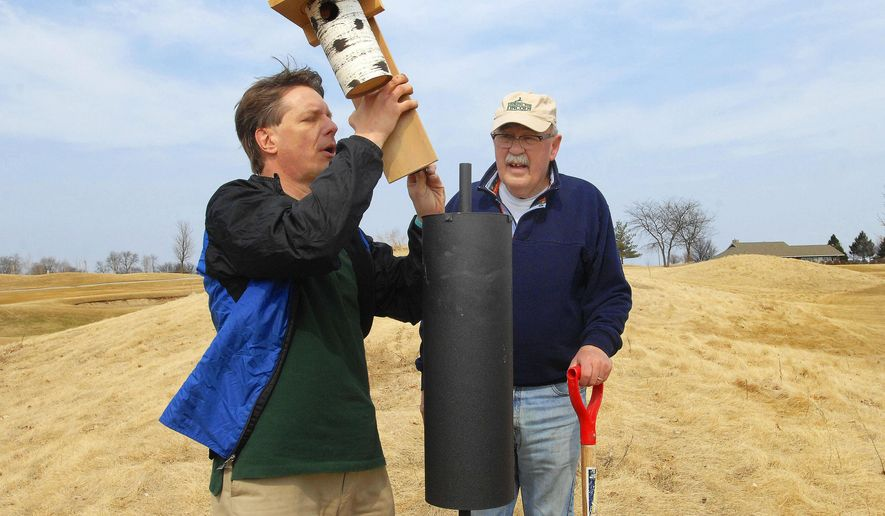 In this March 12, 2015 photo, Frank Zimmerman, left,  and Guy Fraker install a bluebird house in the rough at Prairie Vista Golf Course in Bloomington, Ill. The houses are designed to keep other species out and create a habitat that will encourage greater numbers of bluebirds in the area. (David Proeber/The Pantagraph via AP)
