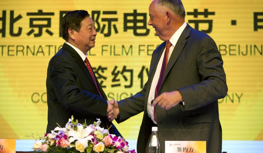 Li Shilin, left, head of China's CITIC Guoan, a unit of state-owned CITIC Group Corporation, and Dick Cook, former Walt Disney Studios Chairman and current head of Dick Cook Studios, shake hands after signing an agreement during a contract signing event held as part of the Beijing International Film Festival in Beijing, Monday, April 20, 2015. Walt Disney Studios signed a deal with CITIC Guoan to invest $150 million into his new Dick Cook Studios. (AP Photo/Mark Schiefelbein)