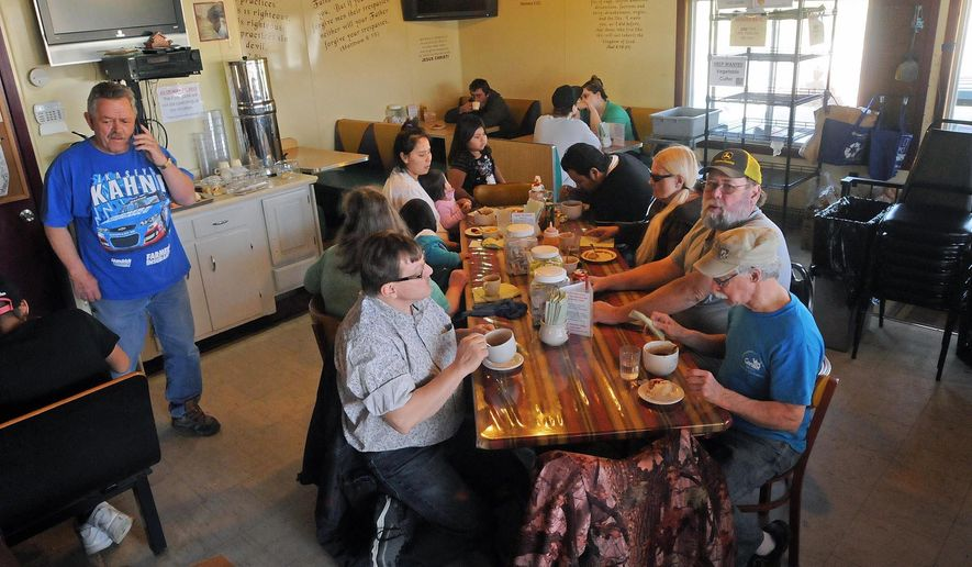 In this undated photo, people eat at the Heaven's Helper's Soup Cafe that serves a large number of people in a converted gas station in Bismarck, N.D. The interior of the cafe has booths and a kitchen where homemade meals are made and provided to people. (Tom Stromme/The Bismarck Tribune via AP)