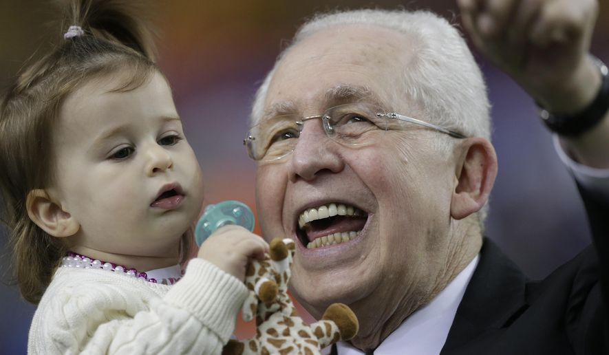 FILE - In this Dec. 2013, file photo, SEC Commissioner Mike Slive holds his granddaughter Abigail before the first half of the Southeastern Conference NCAA football championship game between Auburn and Missouri in Atlanta. The outgoing SEC Commissioner is tackling the final three months of his tenure after undergoing radiation and chemotherapy treatment for prostate cancer, along with back surgery. (AP Photo/Dave Martin, File)