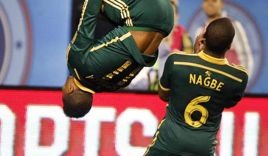 Portland Timbers' Dairon Asprilla (11), of Colombia, does a flip in front of teammate Darlington Nagbe (6), of Liberia, to celebrate scoring agains New York City FC during an MLS soccer game at Yankee Stadium, Sunday, April 19, 2015, in New York.  (AP Photo/Jason DeCrow)
