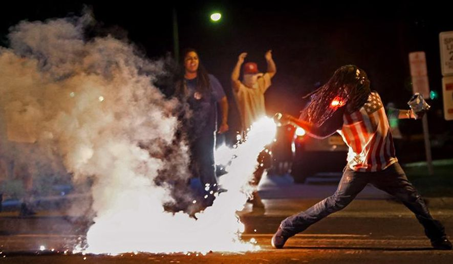 This August 13, 2014, photo by St. Louis Post Dispatch photographer Robert Cohen shows Edward Crawford returning a tear gas canister fired by police who were trying to disperse protesters in Ferguson, Missouri.  Four days earlier, unarmed black teenager Michael Brown was shot to death by white police officer Darren Wilson. The killing ignited riots and unrest in the St. Louis area and across the nation. Cohen and members of the St. Louis Post Dispatch photo staff are winners of the 2015 Pulitzer Prize for Breaking News Photography it was announced Monday, April 20, 2015, at Columbia University in New York. (Robert Cohen, St. Louis Post Dispatch, Columbia University via AP)