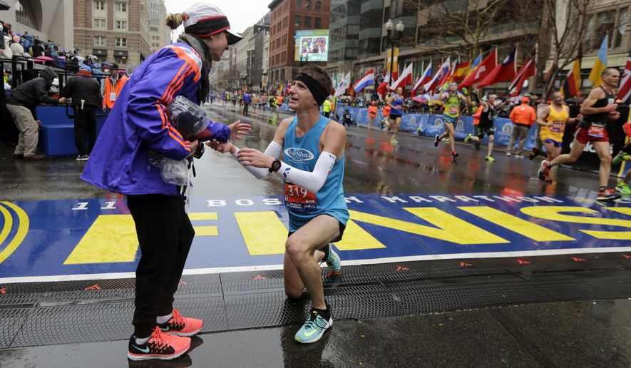 Dustin Hicks, right, of Temple Terrace, Fla., proposes to Laura Bowerman after crossing the finish line of the Boston Marathon, Monday, April 20, 2015, in Boston. (AP Photo/Elise Amendola)