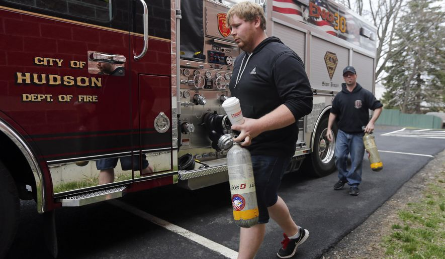 In this Friday, April 17, 2015 photo, volunteer firefighters Rodney Pulver and Fred Goodnow carry air bottles to be filled in Hudson, N.Y. More new firefighters are volunteering in New York state after years of declining membership, though companies are still seeking recruits to meet more calls. (AP Photo/Mike Groll)