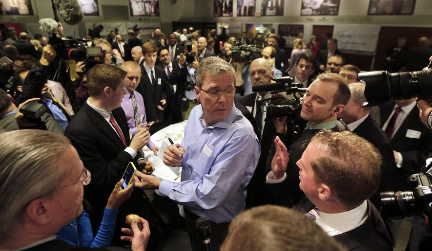 """Former Florida Gov. Jeb Bush, center, mingles at a """"Politics and Eggs"""" event, a breakfast fixture for 2016 presidential prospects, Friday, April 17, 2015, at Saint Anselm College in Manchester, N.H. (AP Photo/Elise Amendola)"""