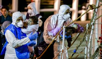 Rescuers help children to disembark in the Sicilian harbor of Pozzallo, Italy, early Monday, April 20, 2015. (AP Photo/Alessandra Tarantino)