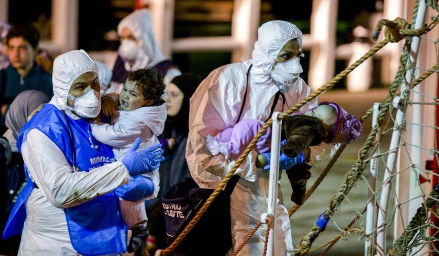 Rescuers help children to disembark in the Sicilian harbor of Pozzallo, Italy, early Monday, April 20, 2015. (AP Photo/Alessandra Tarantino)