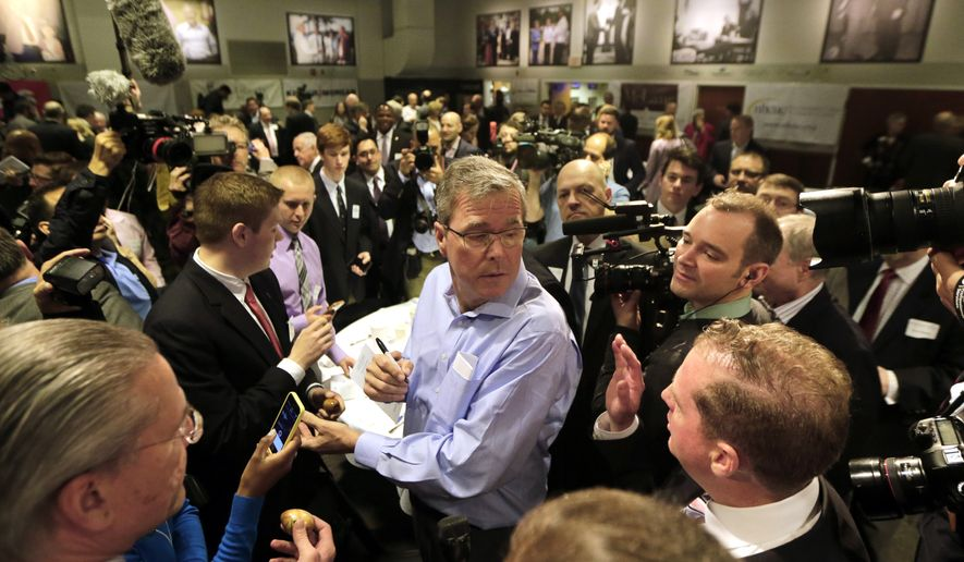 "Former Florida Gov. Jeb Bush, center, mingles at a ""Politics and Eggs"" event, a breakfast fixture for 2016 presidential prospects at Saint Anselm College in Manchester, N.H., in this April 17, 2015, photo. (AP Photo/Elise Amendola)"