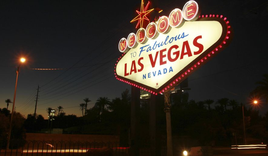 "File - In this Oct. 4, 2012, file photo, the ""Welcome to Fabulous Las Vegas"" neon sign is outlined in pink lightbulbs in honor of breast cancer awareness month in Las Vegas. Betty Willis, the woman who designed the iconic neon sign that has welcomed countless visitors to Las Vegas since 1959 has died. She was 91. (Sam Morris/Las Vegas Sun via AP, File)"