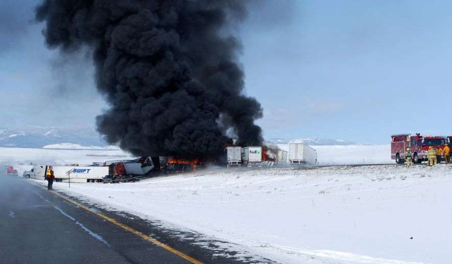 In this photo provided by the Wyoming Highway Patrol smoke rises following the aftermath of a chain-reaction crash along Interstate 80 near Laramie, Wyo., Monday, April 20, 2015. Monday's pileup occurred around 8 a.m., when two commercial trucks crashed, causing one to jackknife in both westbound lanes, Wyoming Highway Patrol Sgt. David Wagener said. (Wyoming Highway Patrol via AP)