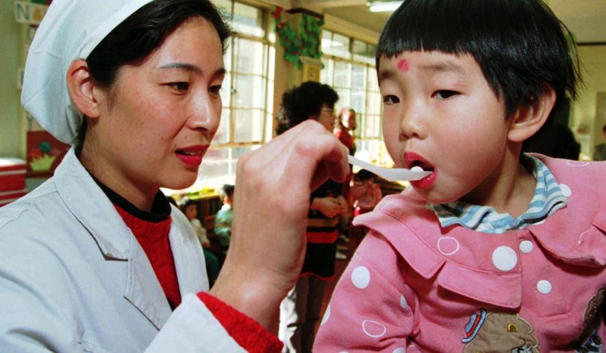 FILE - In this Wednesday, Dec. 6, 1995 file photo, Dr. Lai Nansha uses a spoon to administer a polio vaccination pill to a child at a kindergarten in Beijing. (AP Photo/Greg Baker)