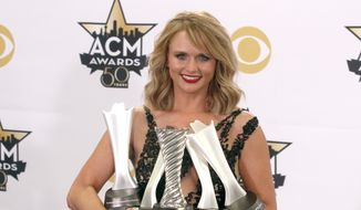 "Miranda Lambert poses in the press room with the milestone award and the awards for song of the year for ""Automatic,"" album of the year for ""Platinum"" and female vocalist of the year at the 50th annual Academy of Country Music Awards at AT&T Stadium on Sunday, April 19, 2015, in Arlington, Texas. (Photo by Jack Plunkett/Invision/AP)"