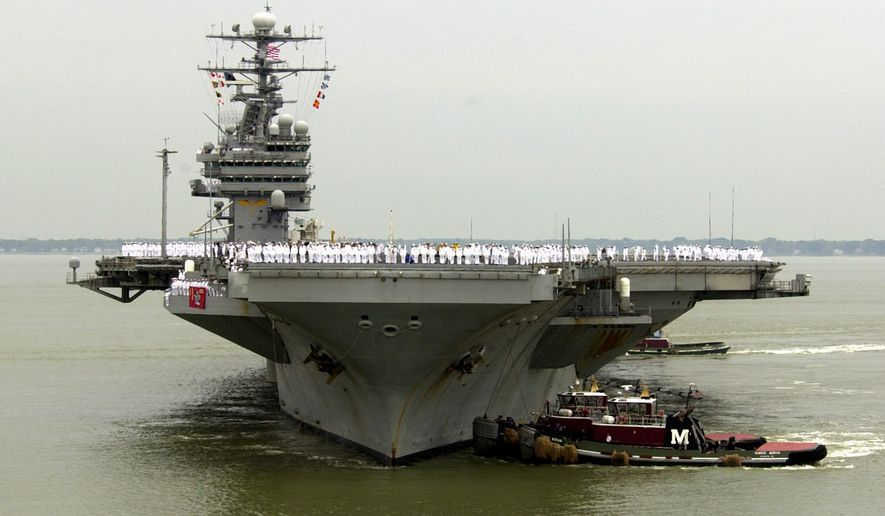 In tbhis May 29, 2003 file photo, sailors man the rails as the USS Theodore Roosevelt is manuvered into it's berth at the Norfolk  Naval Station in Norfolk, Va. (AP Photo/Steve Helber, File)