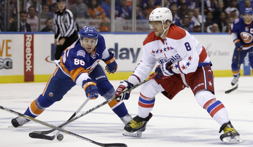 New York Islanders' Nikolay Kulemin, left, tries to get the puck away from Washington Capitals' Alex Ovechkin during the first period of Game 3 of a first-round NHL hockey playoff series Sunday, April 19, 2015, in Uniondale, N.Y. (AP Photo/Seth Wenig)
