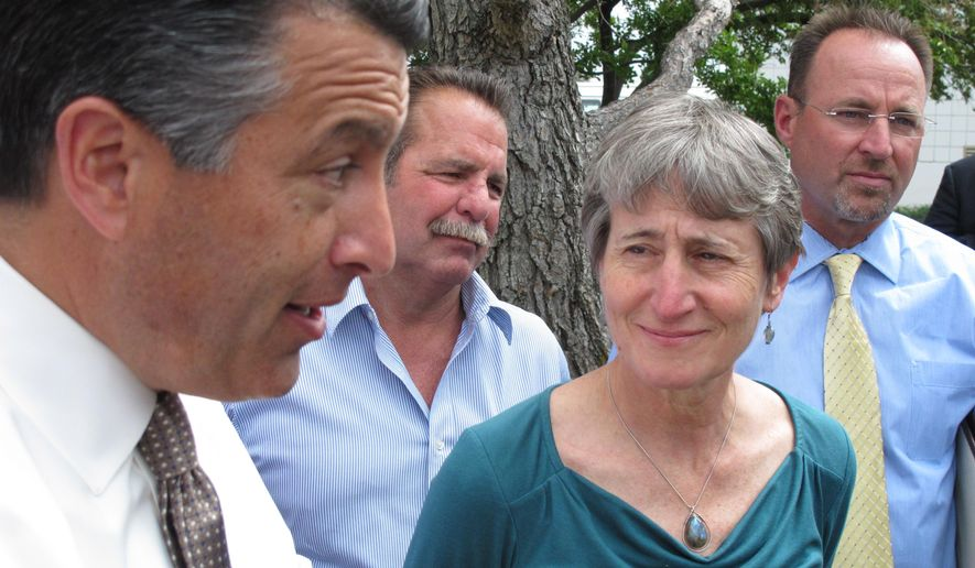 U.S. Interior Secretary Sally Jewell, right, looks on as Nevada Gov. Brian Sandoval, left, answers questions from reporters in Reno, Nev., Tuesday, April 21, 2015 after she announced her reversal of proposed federal protection of the bistate sage grouse along the California-Nevada line. Jewell says withdrawal of a proposal to declare the bird unique to Nevada and California as threatened should be encouraging for those trying to head off a bigger listing decision looming for greater sage grouse in 11 western states. (AP Photo/Scott Sonner)