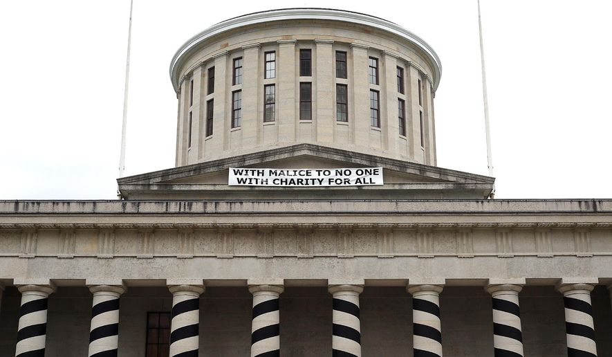 """A misquoted Lincoln phrase is displayed in a banner marking the 150th anniversary of Abraham Lincoln's death atop the west side of the Ohio Statehouse, Monday, April 20, 2015 in Columbus, Ohio.  said in his second inaugural address, """"With malice toward none, with charity for all.""""  A spokesman for the Capitol Square Review and Advisory Board tells The Columbus Dispatch that officials wanted the banner to be historically faithful to the original one that was hung on the building on April 29, 1865. The current banner also is displayed on the building's west portico, just like the 1865 banner that misquoted Lincoln. (Chris Russell/The Columbus Dispatch via AP)"""