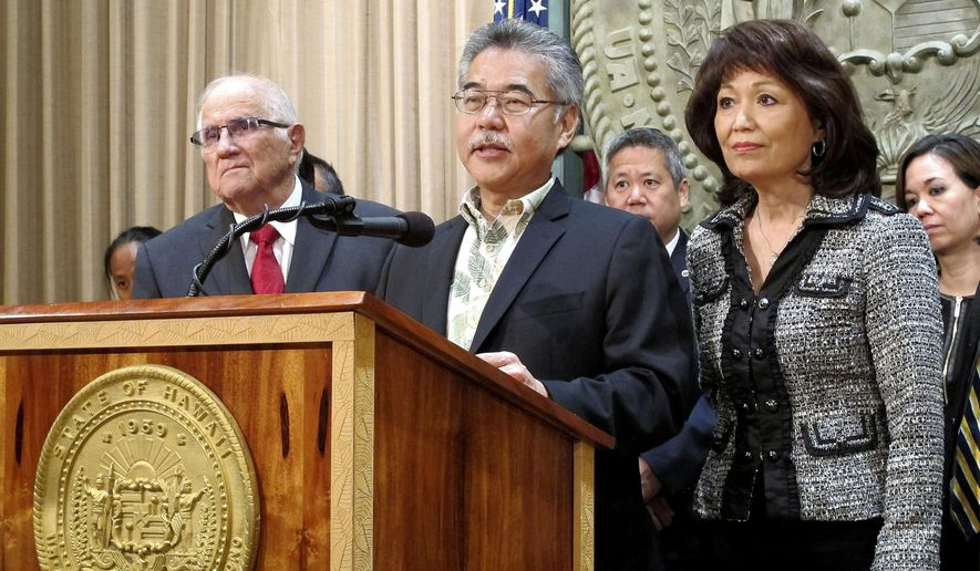 Hawaii Gov. David Ige, center, speaks about Maui's public hospitals with House Speaker Joseph Souki, left, and Senate President Donna Mercado Kim, right, at a news conference in Honolulu, Tuesday, April 21, 2015. Ige intervened in a legislative plan to allow Maui's regional hospitals to be taken over by a private entity just before a scheduled vote in the House of Representatives. (AP Photo/Cathy Bussewitz)