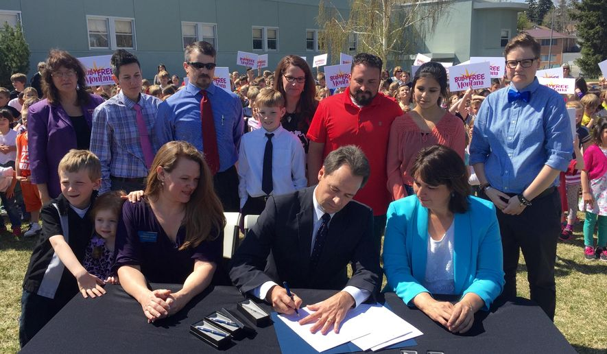 Montana Gov. Steve Bullock signs the Bully Free Montana Act Tuesday, April 21, 2015 at Jefferson Elementary in Helena, Mont., while bill sponsor Rep. Kim Dudik, left, and Superintendent of Public Instruction Denise Juneau look on.  Lawmakers have been trying to pass some form of the measure since 2003 with opponents saying it would infringe on school districts' ability to enact local rules. Forty-six of the 49 states that have established bullying laws did so by 2010. (AP Photo/Lisa Baumann)