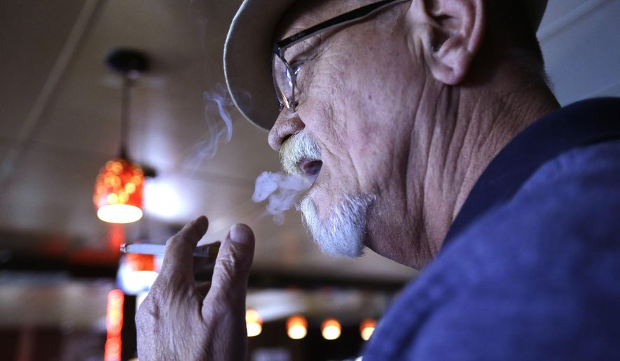 Barry Rutherford smokes a cigarette inside Kajun's Pub, Tuesday, April 21, 2015, in New Orleans. Starting at midnight Tuesday, smoking will no longer be permitted in bars, gambling halls and many other public places such as hotels, workplaces, private clubs and stores. (AP Photo/Gerald Herbert)
