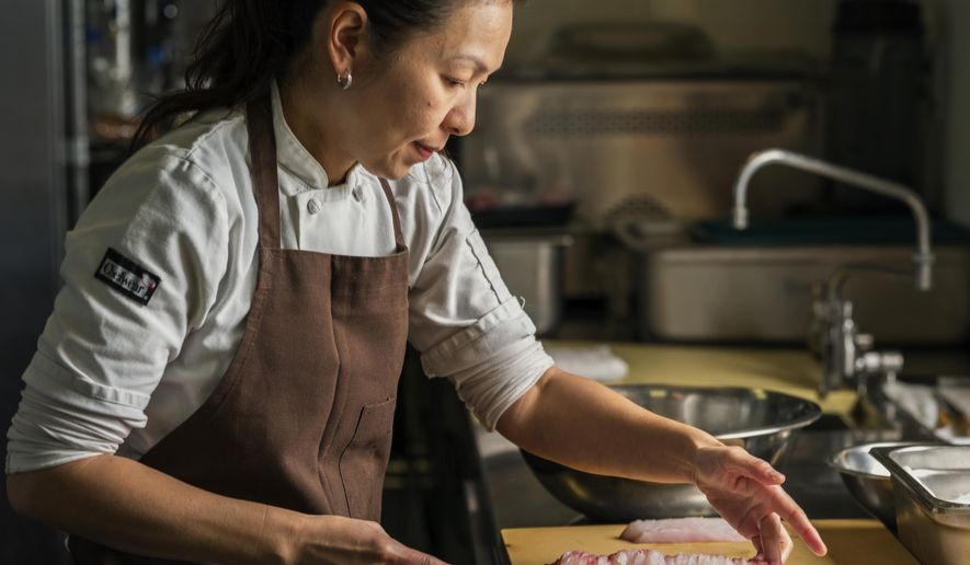 "In this Thursday, April 9, 2015 photo, chef Niki Nakayama cuts fish at her n/naka restaurant in Los Angeles. Chef Niki Nakayama is one of just six chefs to be profiled on Netflix's first homegrown documentary series, ""Chef's Table,"" which features some of the most innovative chefs cooking today. (AP Photo/Damian Dovarganes)"