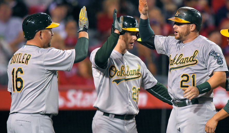 Oakland Athletics' Stephen Vogt, right, is congratulated by Billy Butler, left, and Mark Canha after hitting a three-run home run during the third inning of a baseball game against the Los Angeles Angels, Monday, April 20, 2015, in Los Angeles. (AP Photo/Mark J. Terrill)