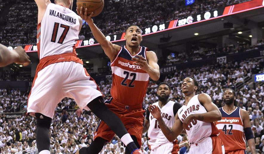 Washington Wizards' Otto Porter Jr. (22) heads for the basket as Toronto Raptors' Jonas Valanciunas (17) defends during the second half in Game 2 in the first round of the NBA basketball playoffs, Tuesday, April 21, 2015,  in Toronto. (Frank Gunn/The Canadian Press via AP)  MANDATORY CREDIT