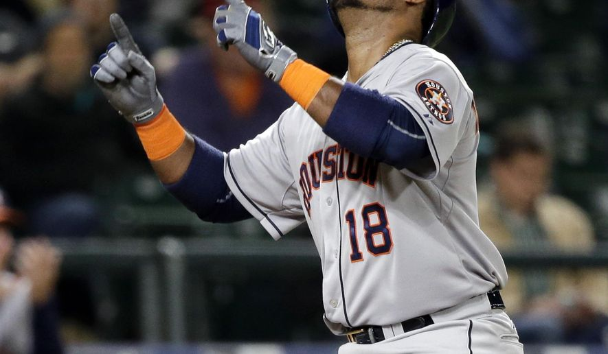 Houston Astros' Luis Valbuena points skyward as he crosses home on his home run against the Seattle Mariners in the eighth inning of a baseball game Monday, April 20, 2015, in Seattle. (AP Photo/Elaine Thompson)