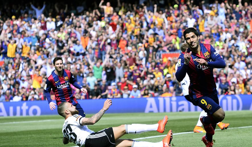 FC Barcelona's Luis Suarez, right, reacts after scoring against Valencia during a Spanish La Liga soccer match at the Camp Nou stadium in Barcelona, Spain, Saturday, April 18, 2015. (AP Photo/Manu Fernandez)
